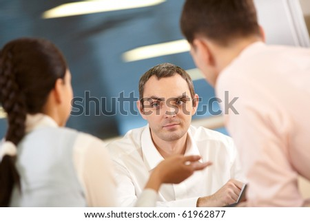 Three businessmen sitting at table and communicating, two of them defocused - stock photo