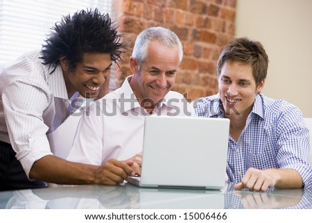 Three businessmen sitting in office with laptop smiling