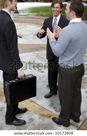 three businessmen standing talking outdoors
