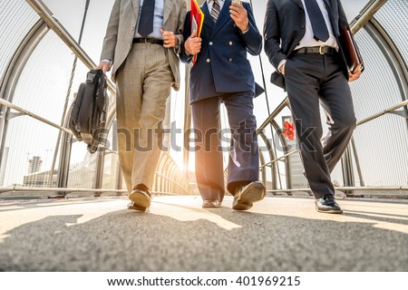 Three businessmen walking in a financial area while having a conversation - Work colleagues going to work - stock photo