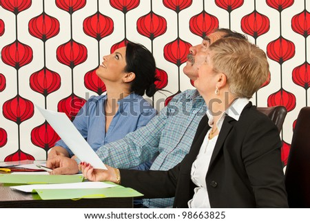 Three businesspeople at meeting looking up in modern office - stock photo