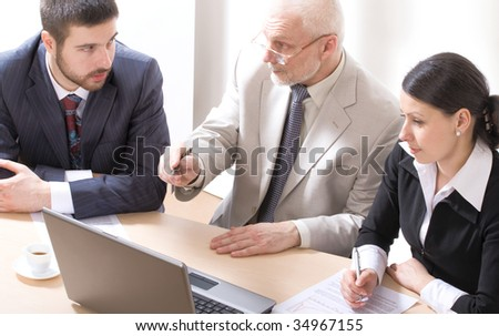 Three businesspeople discussing computer work - stock photo