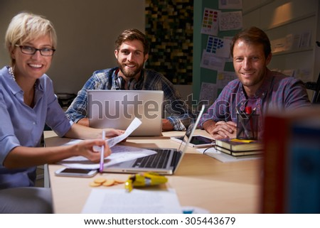 Three Businesspeople Having Late Meeting In Office - stock photo