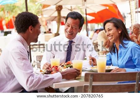 Three Businesspeople Having Meeting In Outdoor Restaurant - stock photo