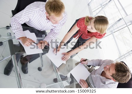 Three businesspeople in boardroom with paperwork - stock photo