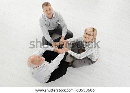 Three businesspeople in smart clothes meditating on floor, concentrating on team force, smiling at camera, overhead view.? - stock photo