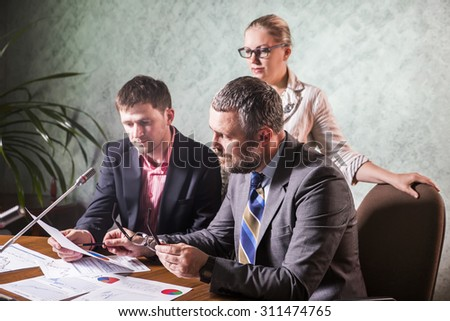 three businesspeople interacting at meeting, colleagues meeting to discuss their future financial plans - stock photo