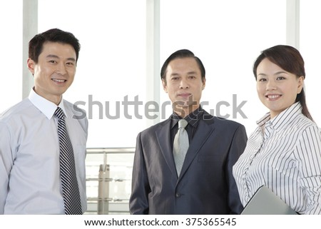 Three Businesspeople Looking at Camera - stock photo