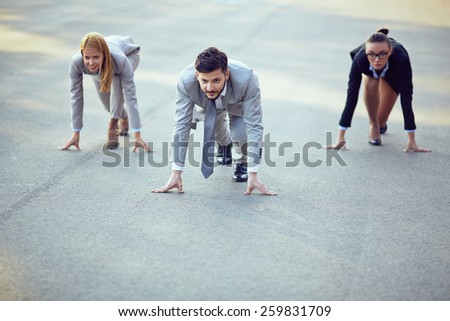 Three businesspeople ready to run - stock photo