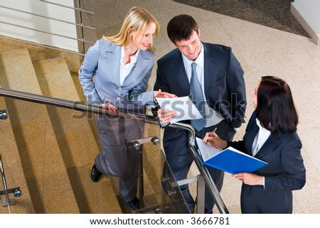 Three businesspeople run across on the stairs of the business building showing documents to each other and making notes - stock photo