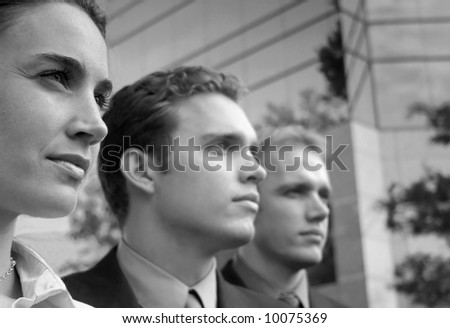 three businesspeople standing facing  same direction - stock photo