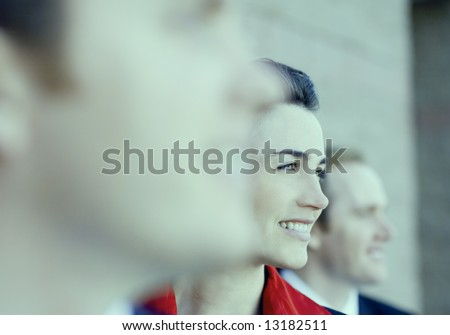 three businesspeople standing in a line with young attractive woman in the middle smiling - stock photo