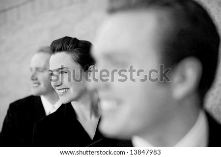 three businesspeople standing in a line with young attractive woman in the middle smiling