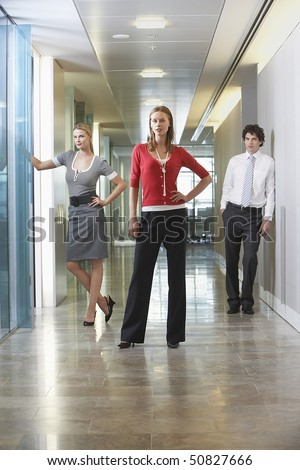 Three businesspeople standing in office corridor, portrait - stock photo