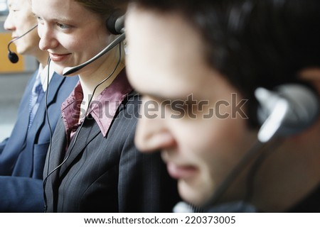 Three businesspeople talking on headsets - stock photo