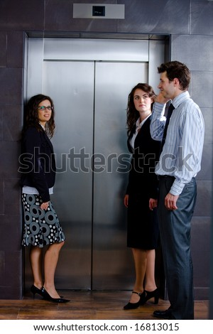 Three businesspeople waiting for the elvator and talking at office lobby. - stock photo