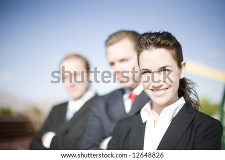 Three businesspeople wearing suits with arms folded looking at the camera - stock photo