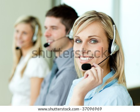 Three businesspeople working with headsets in an office - stock photo