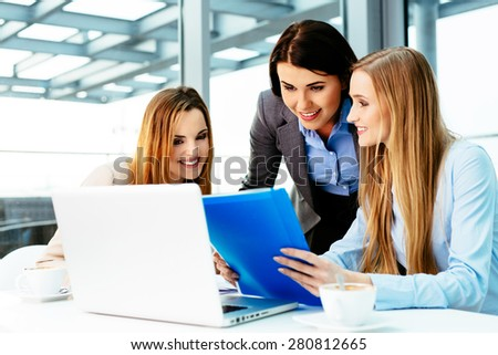 Three businesswomen at office working with laptop - stock photo