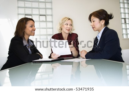 Three businesswomen sitting at office desk having meeting and discussing paperwork. - stock photo
