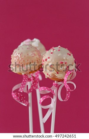 three Cake pops mixed   and a pink ribbon with white polka dots on a pink background 1