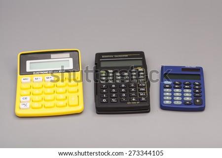 three calculators isolated on gray background - stock photo