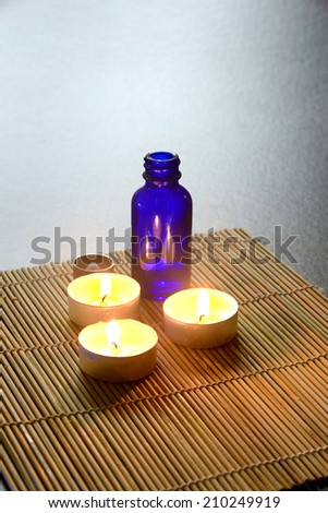 Three candle a blue bottle/Healing Ointment/Three candles on a bamboo mat - stock photo