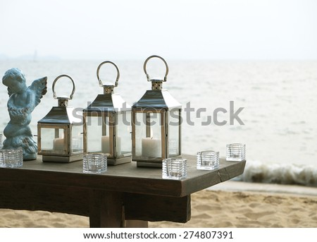 three candle light and cupid statue with the beach background