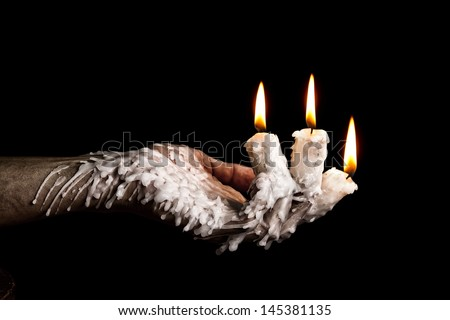 Three candle sticks on fingers bunring with wax flow artistic conversion - stock photo