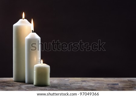 Three Candles against Dark Background - stock photo