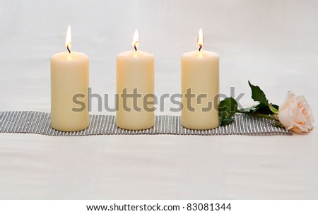 Three candles and a pink rose. - stock photo