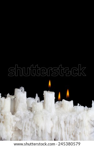 three candles burning on a black background with space for text