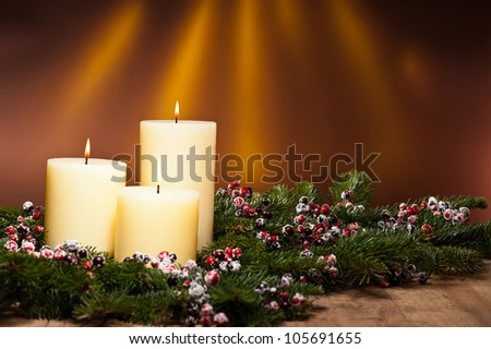 Three candles in an advent flower arrangement for advent and Christmas on a wooden surface - stock photo