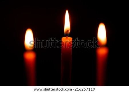Three candles on black background