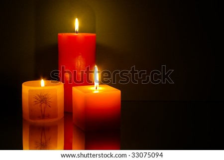 Three candles on green background