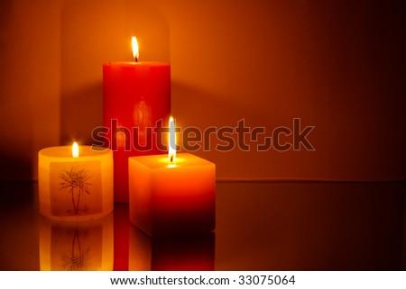 Three candles on orange background - stock photo