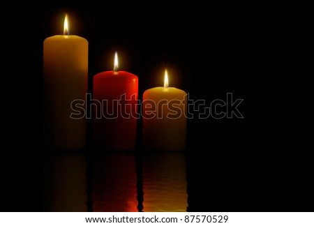 Three candles over a black background and its reflection - stock photo