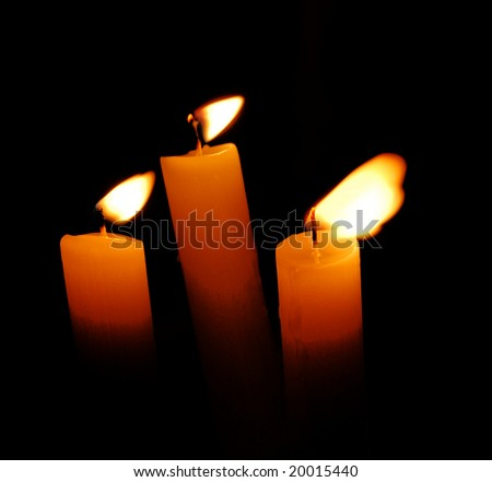 three candles over black background
