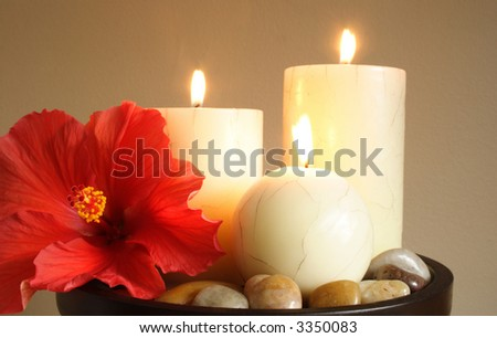 Three candles sorrounded with pebbles in  a tropical relaxation atmosphere - stock photo