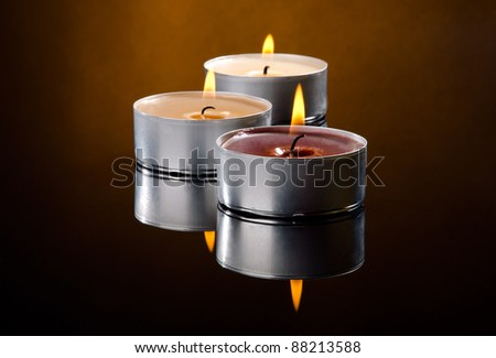 Three candles with brown background - stock photo
