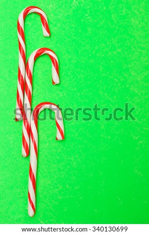 Three candy canes on a green background