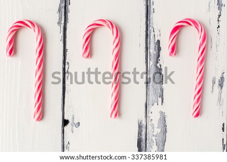 three candy canes on white wooden background - stock photo