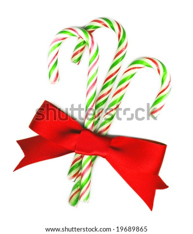 Three candy canes with red bow on white background isolated, Christmas background - stock photo