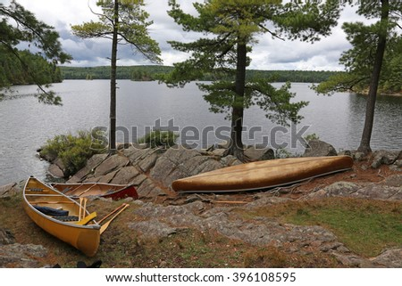 Three canoes on the edge of a lake in Algonquin Provincial Park, Ontario, Canada.  - stock photo