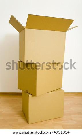 Three cardboards standing on the floor. Front view, gray background - stock photo