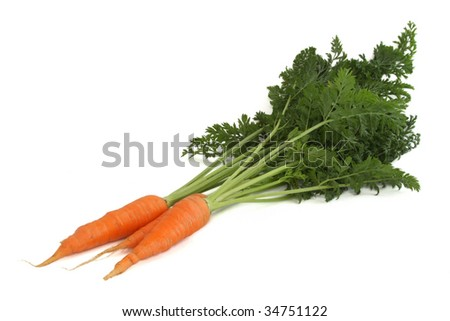 Three carrots with leaves isolated on white - stock photo