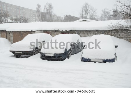 Three cars covered with snow in the winter blizzard on the street of city