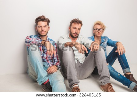 three casual men having a break and rest sitting down on the floor of the studio - stock photo