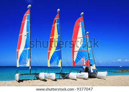 three catamaran's lined up on a beach with the owners in Barbados, just waiting to be hired