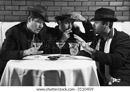 Three Caucasian prime adult males in retro suits sitting at table drinking and smoking and talking. - stock photo